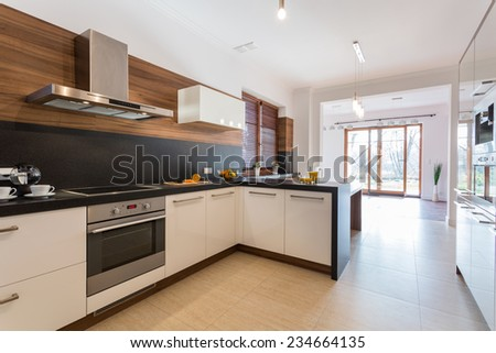 Modern clean kitchen open on bright spacious dining room