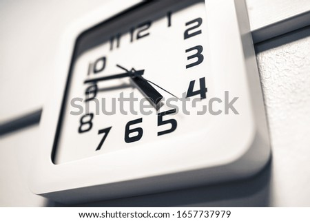 Modern clock on a wall. Almost 5 o'clock in the afternoon or morning. Over time at work. Dramatic angle. Foto stock ©