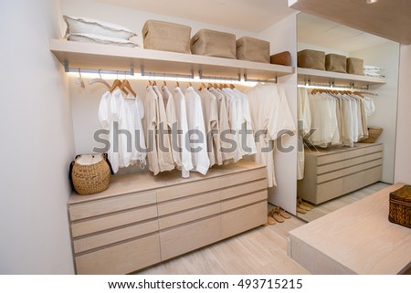 modern closet with row of white shirt hanging in wardrobe