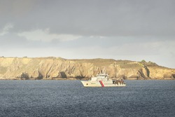 Modern coast guard ship sailing near the rocky shores (cliffs) of Brittany, France. Border control, international security, global communications, military, lockdown, navigation, special equipment