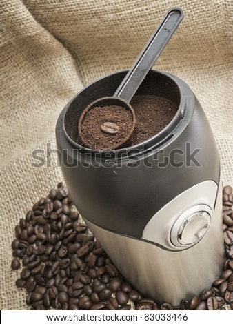 Modern coffee grinder with beans on burlap