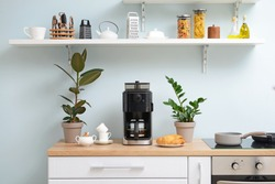 Modern coffee machine, cups and croissants on kitchen table