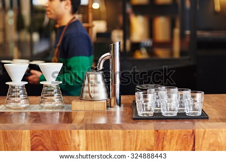 Modern coffee shop counter with glasses, coffee filters, and hot water kettle waiting for use on the wooden surface with a barista visible in the background
