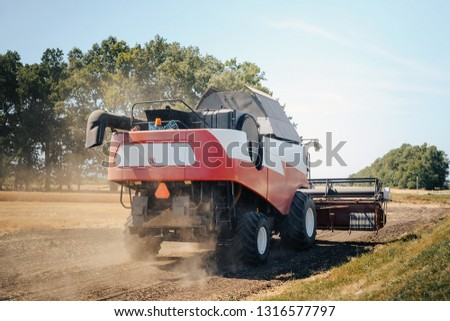 Modern combine harvester rides on the harvested field. #1316577797