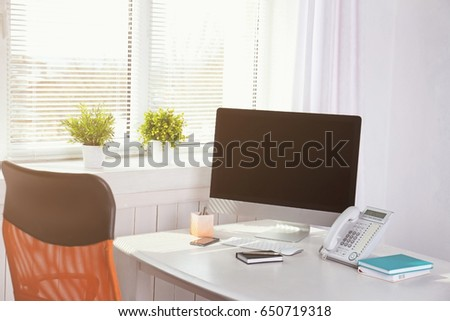 Modern comfortable workplace with computer and window blinds #650719318