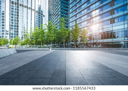 Modern commercial buildings and urban green landscape belts.