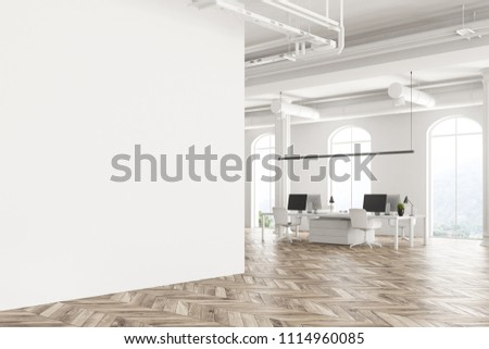 Modern company office interior with white computer tables, arched windows and a wooden floor. Concept of interior design. Angle view. Blank advertisement wall. 3d rendering mock up.