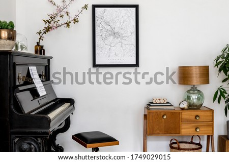 Modern composition of home interior with stylish black piano, design cabinet, cacti, flower, lamp, decoration, mock up poster map and elegant personal accessories in stylish home decor.