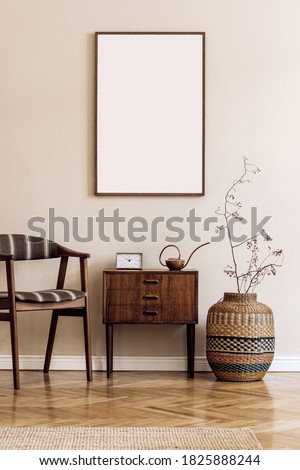 Modern composition of living room interior with brown mock up poster frame, design retro commode, chair, etno basket with flower and elegant accessories. Template. Stylish home staging. Japandi.