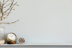 Modern composition on the shelf with dried flower in design vase, gold clock, accessories and decoration. Grey wall. Copy space.