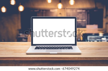 Modern computer,laptop with blank screen on table with blur cafe,restaurant backgrounds