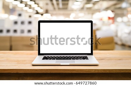 Modern computer,laptop with blank screen on table with blur store factory background