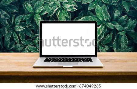 Modern computer,laptop with blank screen on table with green leaf backgrounds