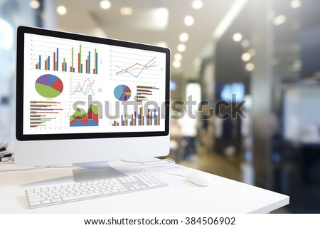 Modern computer with keyboard and mouse on table showing charts and graph against office background in blue tone, Analysis Business, Statistics Concept.