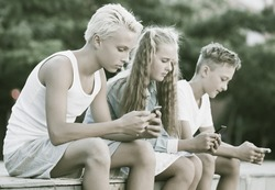 Modern concentrated kids spending time together outdoors using mobile gadgets