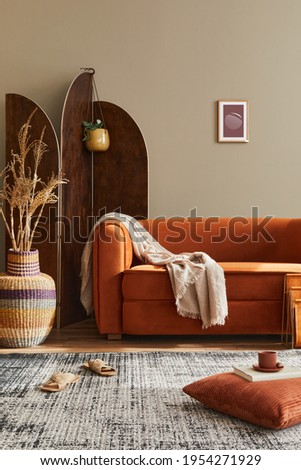 Modern concept of domestic interior with design sofa, wooden room screen, pillow, blanket, picture frame ,wooden stool and elegant personal accessories in stylish home decor. Template.