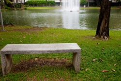 modern concrete bench in the garden near the pond