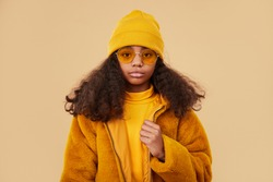 Modern confident African American teen girl in trendy glasses wearing yellow coat and sweater with knitted hat looking at camera on beige background