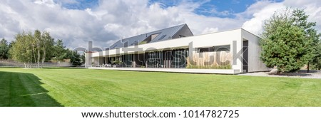 Modern construction of big luxurious home with grass and trees around
