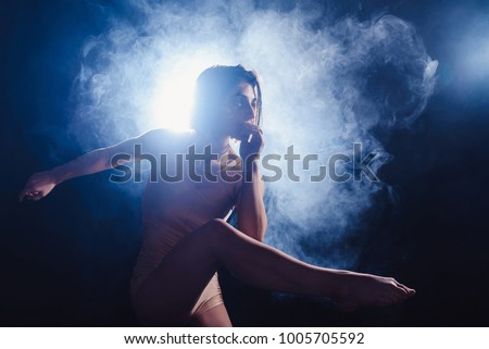 Modern contemporary dancer poses in front of the studio black background with the smoke. pose with the leg #1005705592