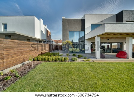 Modern country house with the large lawn and a wooden fence. In front of the house there is a covered terrace with a lounge zone. On the lawn there is a trees and flowerbeds. It is sunny. Outside.