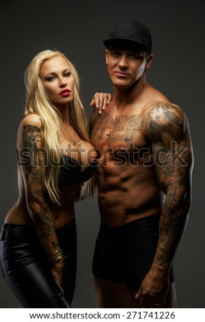 Modern couple with tattooed bodies posing in studio