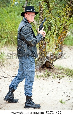 modern cowboy standing on sand, trees on background