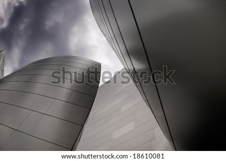 modern curved building with metal on a dark cloudy sky