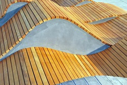 Modern curved s shaped brown wooden bench outdoor furniture detail as background image