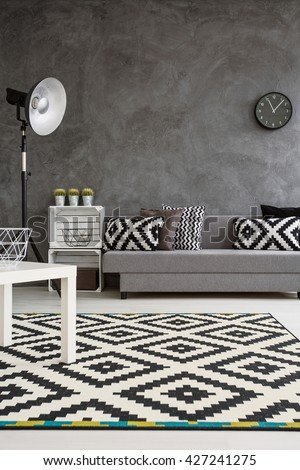 Modern decor of living room with grey walls and black and white carpet on wooden floor