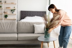 Modern Decoration Concept. Casual young lady putting glass vase with dried flowers on tea table. Millennial woman decorating her modern apartment and bedroom or living room with pampas grass