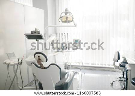 Modern dental cabinet in white colors. Defferent dental equipment, chair, lamp, drill machines. Concept dental treatment