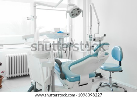 Modern Dental Clinic, Dentist chair and other accessories used by dentists in blue medical light. Dental surgeon, is a surgeon who specializes in dentistry and treatment of conditions of oral cavity.