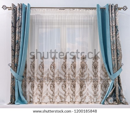Modern design of a small window. Combined curtain with eyelets, monochromatic turquoise fabric, tapestry with an ornament and a tulle with patterns hang on a round cornice. #1200185848