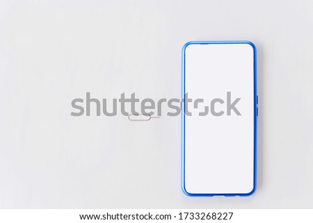 Photo of  Modern design smartphone with sim card tools, Eject pin sim card tray on white background.