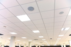 Modern design white office ceiling with white tiles and lighting
