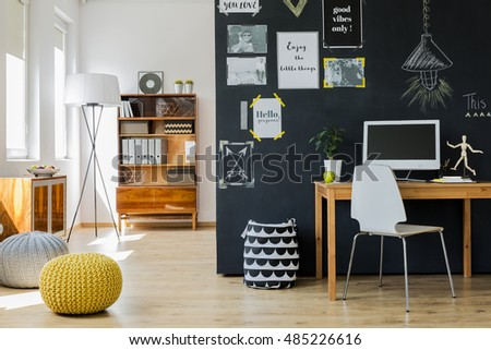 Modern designed, bright room with a black wall with motivational posters on, with wooden desk, minimalistic chair, wooden case and poufs