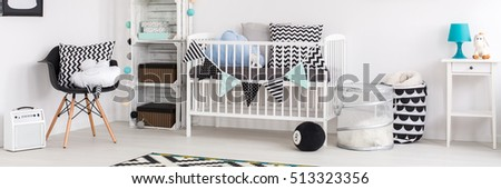Modern designed child room with black and blue decorations for little boy. White cradle with pillows and shelf with boxes #513323356