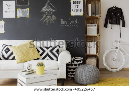 Modern designed room interior with a black wall with motivational posters on, white couch with cushions, yellow carpet, coffee table made from the wooden chest and white, fashionable bicycle #485226457