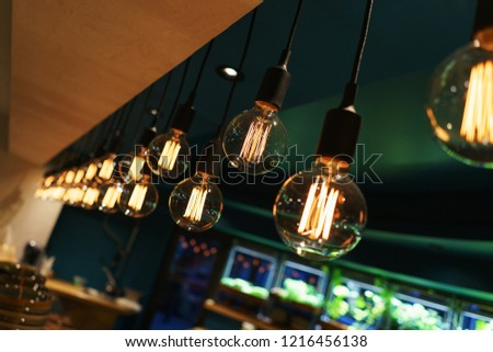 Modern designer incandescent lamp for lighting the room. Details of the design and lighting of the modern interior. Glass lamp on the wire. Soft focus and beautiful bokeh.
