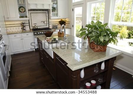 Modern designer kitchen with a hardwood floor and granite island. - stock photo