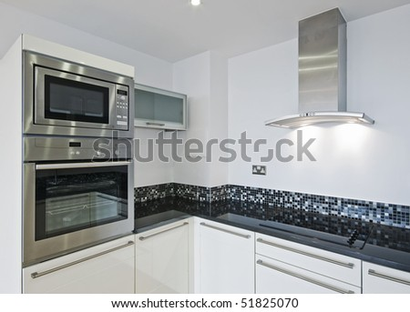 modern designer kitchen with electric appliances stone worktop and mosaic tiles