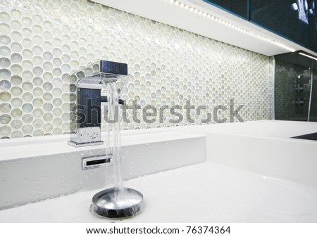 modern designer  tap with running water and mosaic wall - stock photo