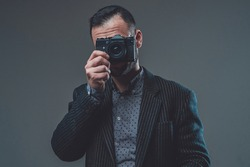 Modern digital camera. Front view of a middleaged guy wearing custom suit and doing shot with his digital camera.