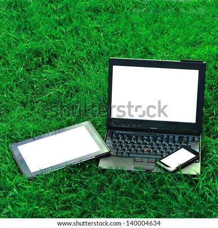 Modern digital tablet PC with mobile smartphone and  laptop on green grass