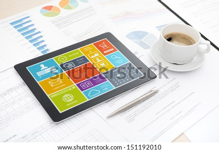 Modern digital tablet with colorful modern widows user interface on a screen lying on a desk with some papers and documents, pen and cup of coffee.