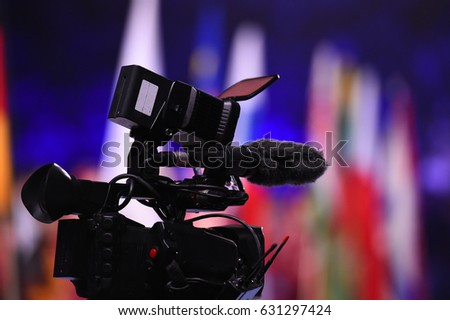 Modern digital television or video camera, camcorder, recorder in studio on blurred colorful background. Broadcasting, media, entertainment