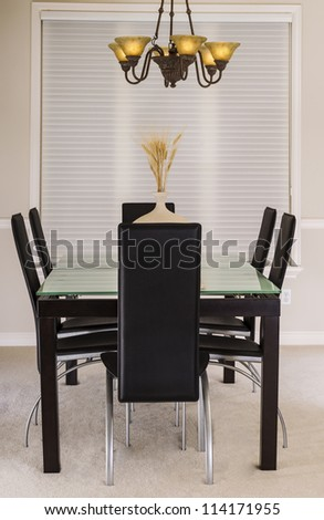 Modern Dining Room with glass top table, leather chairs, chandelier and large window in background