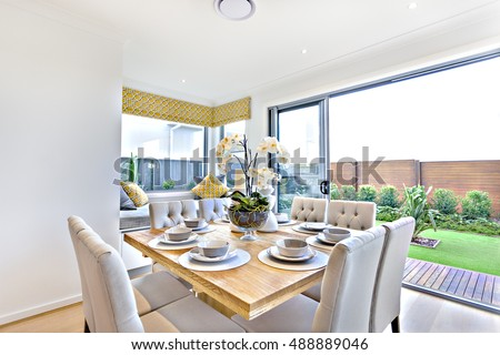 Modern dining table set up indoors with outdoor garden view in a luxury house, shiny wooden table in brown color has ceramic cups and dishes with a glass vase and flowering plant decoration,  #488889046