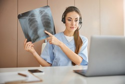 Modern doctor holding an x-ray image while having a video-call on her laptop